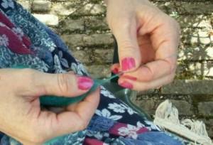 """La main gauche (la plus proche de la bobine) quant à elle vérifie le bon degré de torsion du fil. C'est la """"main d'en haut"""". Le fil est maintenu entre le pouce et l'index."""