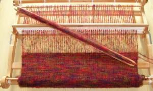 Métier à tisser à peigne envergeur avec tissage en cours.